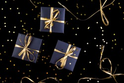 Black gift boxes with gold ribbon on shine background. Flat lay