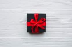 Black gift with red ribbon and bow, isolated on blue background. Present box on wooden board. Space for text. Black Friday super sale shopping.