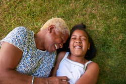 Black girl and grandmother lying on grass, overhead close up