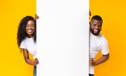 Black Girl And Guy Holding White Advertising Board, yellow studio background, panorama
