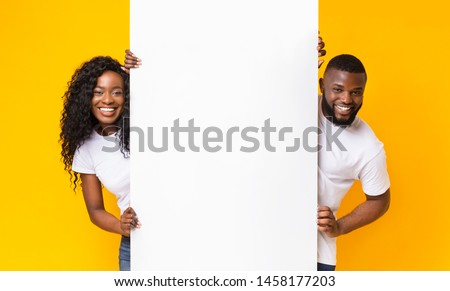 Black Girl And Guy Holding White Advertising Board, yellow studio background, panorama #1458177203