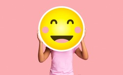 Black girl hiding face behind happy shy emoji emoticon, standing over pink studio background with copy space