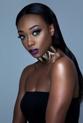 black girl in large necklace and make up