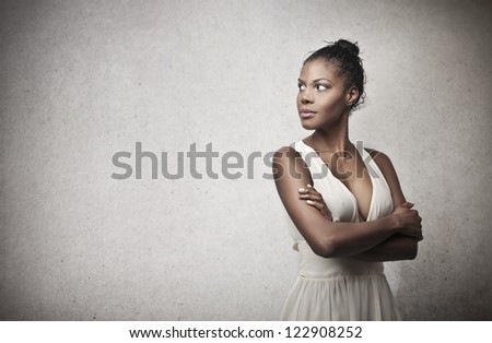 Black girl in white with her arms folded