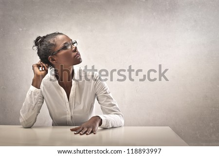 Black girl, leaning on a white desk, thinks