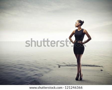 Black girl posing in black on a pier