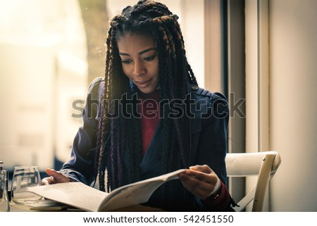 Black girl reading the menu in a bar #542451550