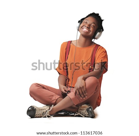 Black girl smiling while listening to the music with a pair of headphones