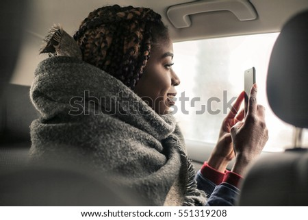 Black girl tking a picture with her phone from the car