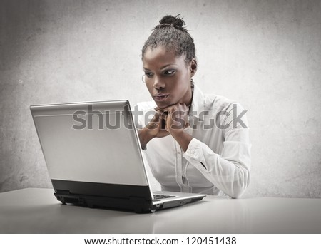 Black girl waiting for an answer in front of a laptop computer