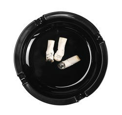 Black glass ashtray with cigarette stubs, butts with ash isolated on white background, top view