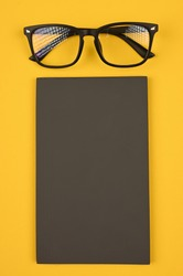 Black glasses and slate board, on yellow background