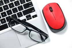 Black glasses on a laptop, red mouse isolated on a white background