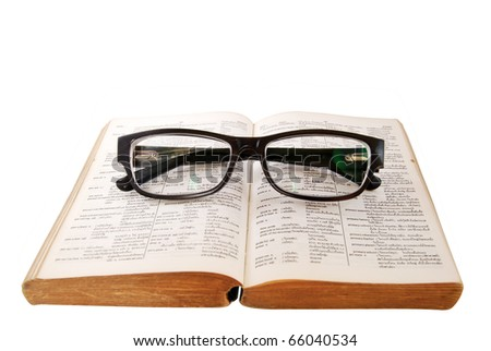 black glasses on old dictionary book isolated on white background
