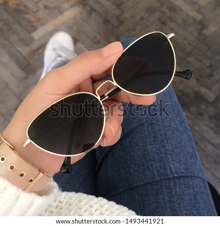 Black glazed women's glasses, golden frame, female hands Stok fotoğraf ©