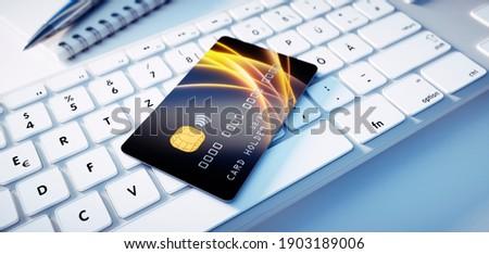 Black glossy credit card mock up lying on computer keyboard - 3D Illustration