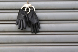 Black gloves holding tied with rusty police handcuffs hanging and moving on steel door closeup.