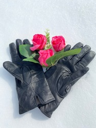 Black gloves with pink roses lie in the snow. Winter hiking, tourism. rest, celebration in nature.