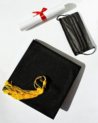 Black graduate cap yellow tassel, paper scroll with red ribbon bow, protective face mask on white background, protection from virus, getting diploma in new reality, new normal, top view, mortarboard