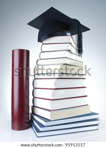Black graduation cap on pile of books with diploma tube