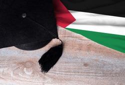 Black graduation hat on Western Sahara flag, education concept, top view