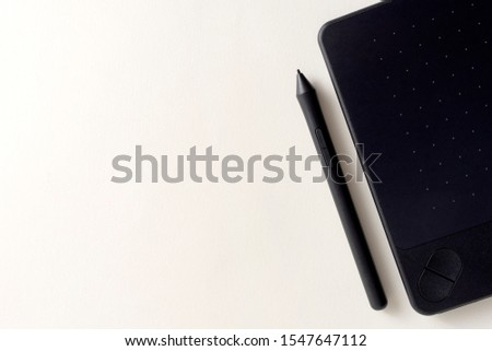 Black graphic tablet with pen for illustrators and designers. Graphic digital touch tablet with White background and stylus pen #1547647112