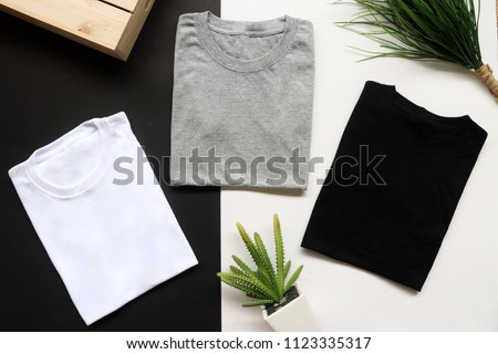 black , gray , white t-shirts with wood box and cactus. rustic background