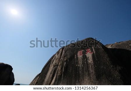 black grey hills rocks under sunshine pure blue sky. Chinese translations: The remotest corners of the globe. famous landmark tourist attraction scenic spot of Sanya city Hainan China.