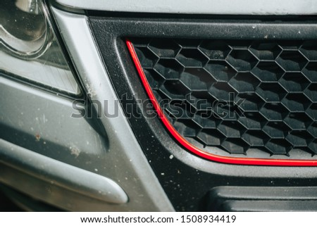 Black grid with red line on a grey car - Hexagonal shaped grille of a modern sport vehicle - Daek automotive aftermarket part made of plastic #1508934419