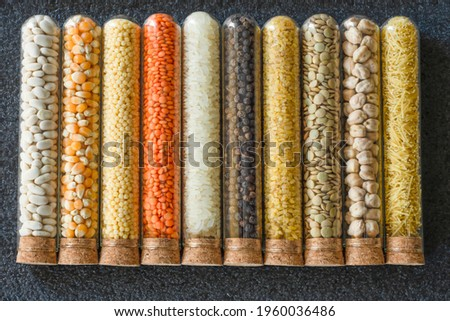 Black ground beans, unexploded corn, couscous pasta, red lentil, rice, chickpeas, vermicelli, green lentils, bulgur in glass bowls with mushroom covers on the ground Stock photo ©