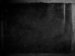 Black grunge scratched scary background with frame, distressed chalkboard, old film effect, copy space
