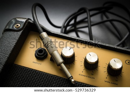 Stock Photo Black guitar amplifier with jack cable on black  background