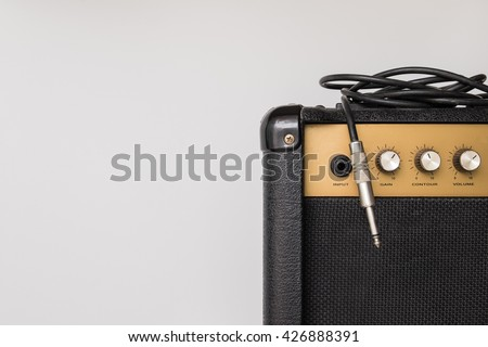 Stock Photo Black guitar amplifier with jack cable on white  background