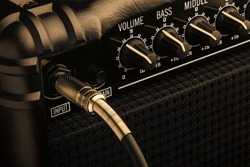 Black Guitar Amplifier with jack plugged in. Close up macro.