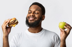 Black Guy Holding Burger And Apple Choosing Between Healthy Vs Unhealthy Food Standing In Studio On White Background. Male Nutrition And Junk Food, Cheat Meal On A Diet Concept