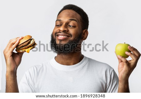 Black Guy Holding Burger And Apple Choosing Between Healthy Vs Unhealthy Food Standing In Studio On White Background. Male Nutrition And Junk Food, Cheat Meal On A Diet Concept Stock photo ©