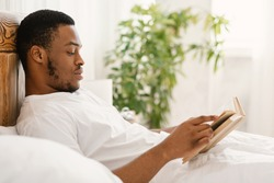 Black Guy Reading Book Lying In Comfortable Bed In Bedroom At Home. African American Man Enjoying Longread Fiction Bestseller Novel Relaxing On Weekend Morning. Read More Concept