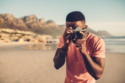 Black guy using digital camera on beach. Afro american man taking pictures on the seashore.