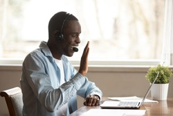 Black guy wear headset start lesson online look at laptop screen wave hand greeting tutor improves foreign language knowledge get skills through internet, education distantly using modern tech concept