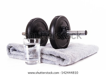 Black gym barbell, dumbbell with disks, blue towel and glass of water, isolated on white background.