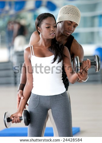 black gym woman lifting freeweights with her personal