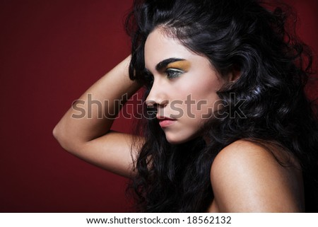 stock photo : Black hair fashion model posing on red background.