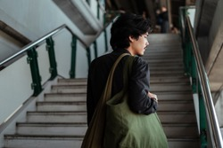 Black hair man on a stair of skytrain station who always uses canvas bag in everyday life.