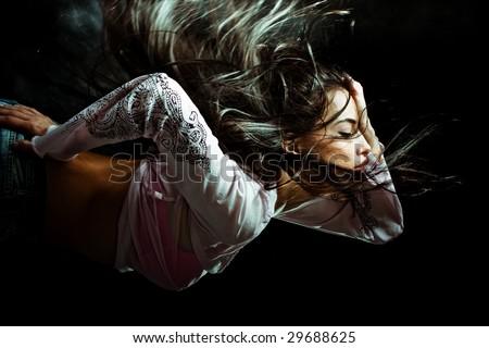 black hair woman with flying hair. studio dark