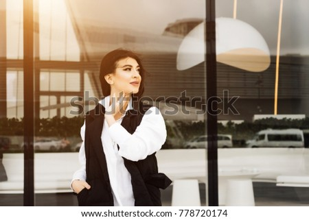 black-haired beautiful girl in a suit and a white shirt posing