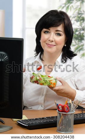 Black haired businesswoman eats healthy vegetable salad for every lunch hour in office. Vertical portrait of middle-aged woman sitting with takeaway transparent container at desk.
