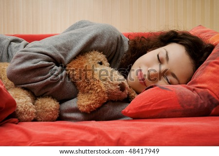 black haired girl lying on the bed with a red sheet. She hugs a stuffed toy dog and smiling in her sleep. Girl dressed in a gray sweatshirt