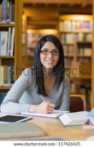 Black-haired woman doing some research in the library