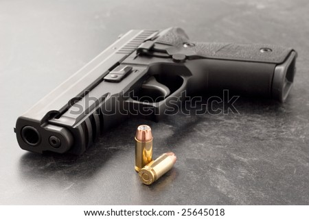 Black hand gun or pistol on black textured surface with hollow point personal defense bullets.