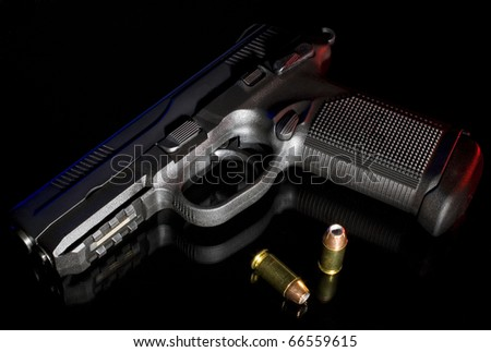 Black handgun with a polymer frame on a reflective surface